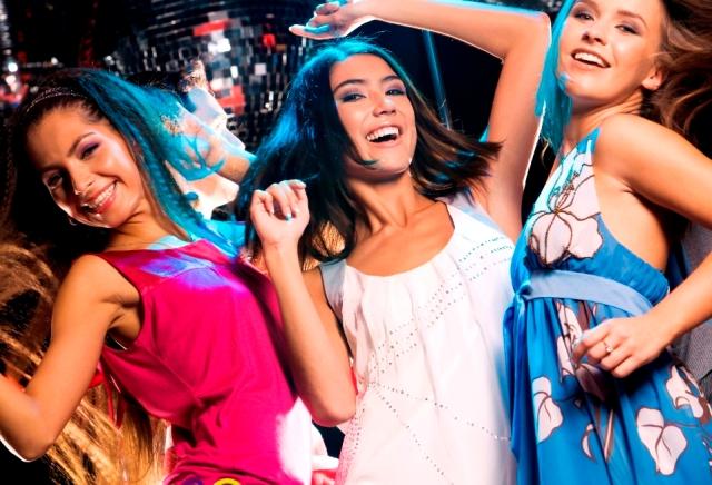 Three glamorous girls enjoying themselves while dancing in night club